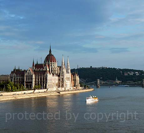 Budapest parliament on the Danube bankside and tourist boat photo
